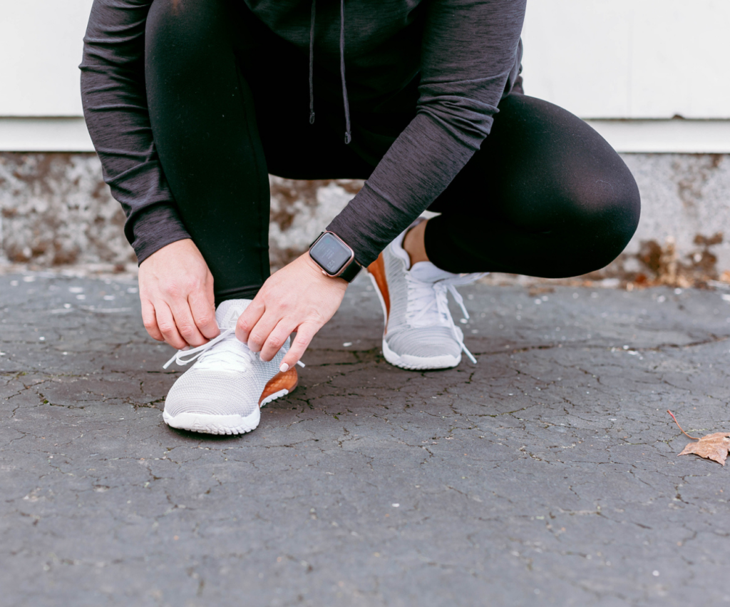 woman tying shoes on the ground
