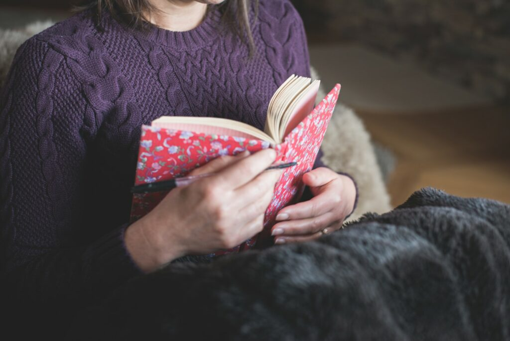 woman in purple sweater with journal