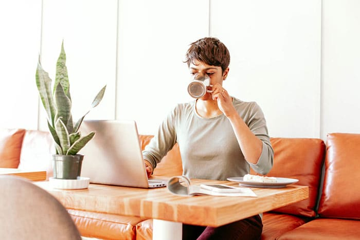 woman drinking coffee while working on her blog