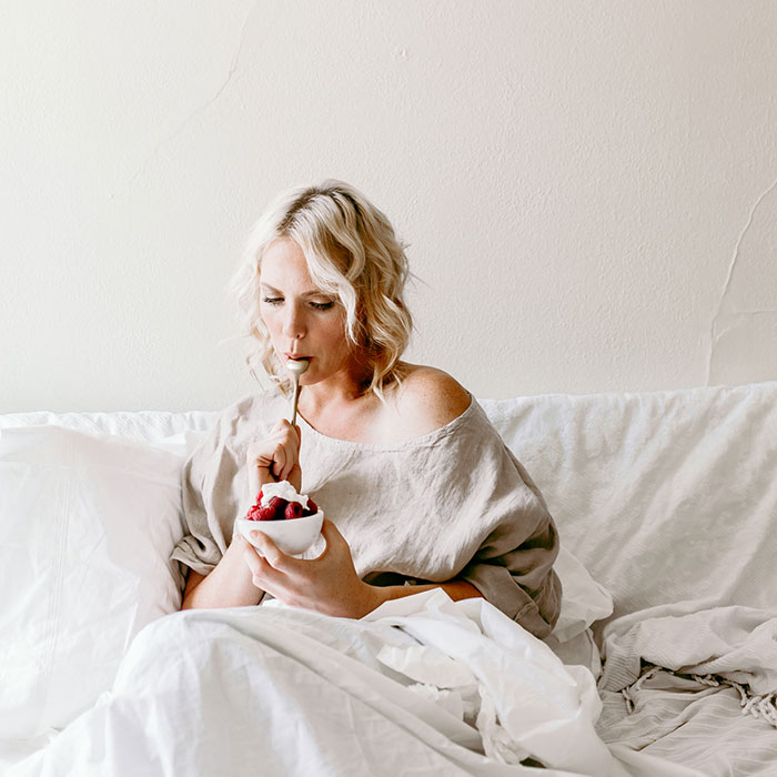 woman in bed eating raspberries with cream