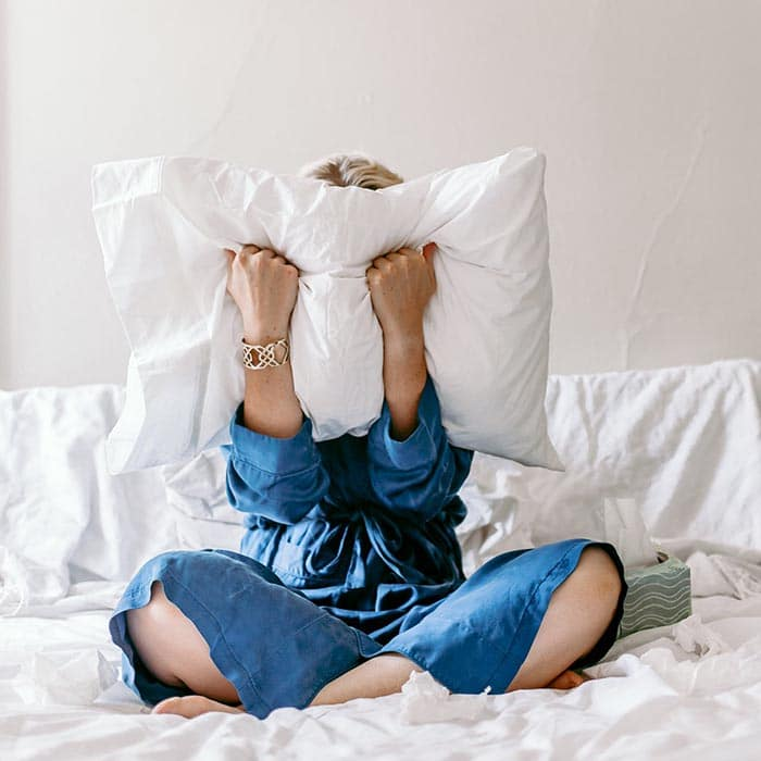woman screaming into a pillow