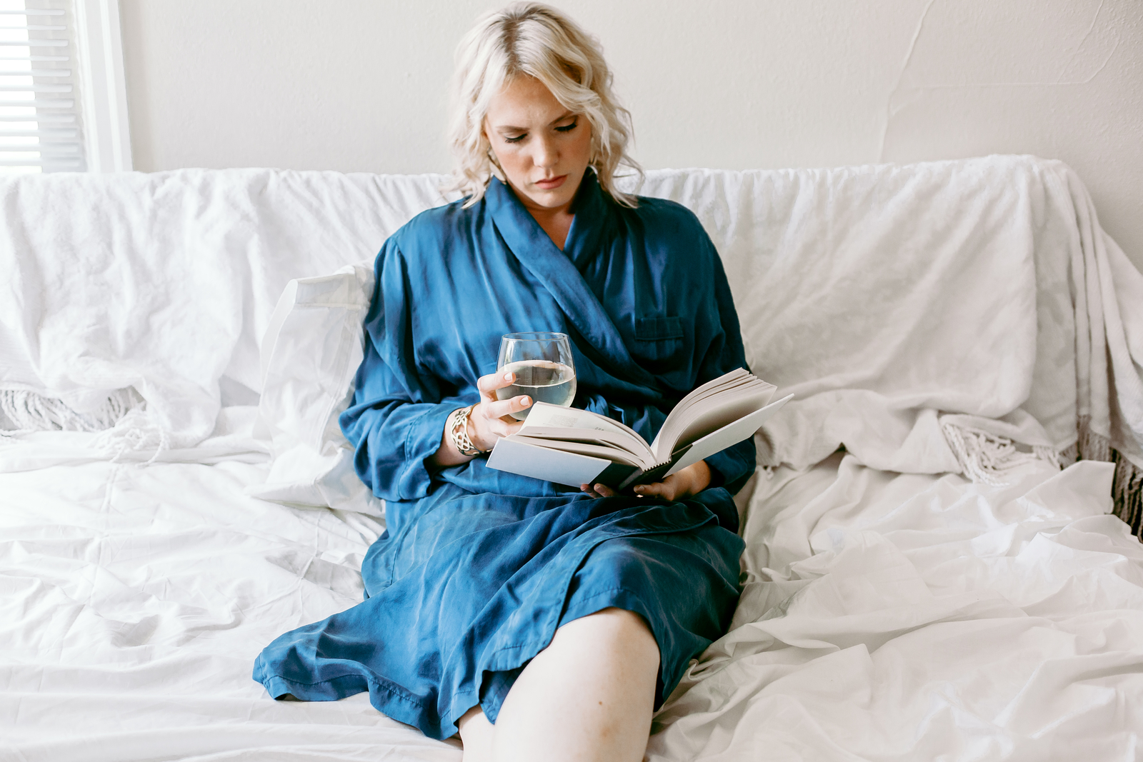 woman laying in bed reading