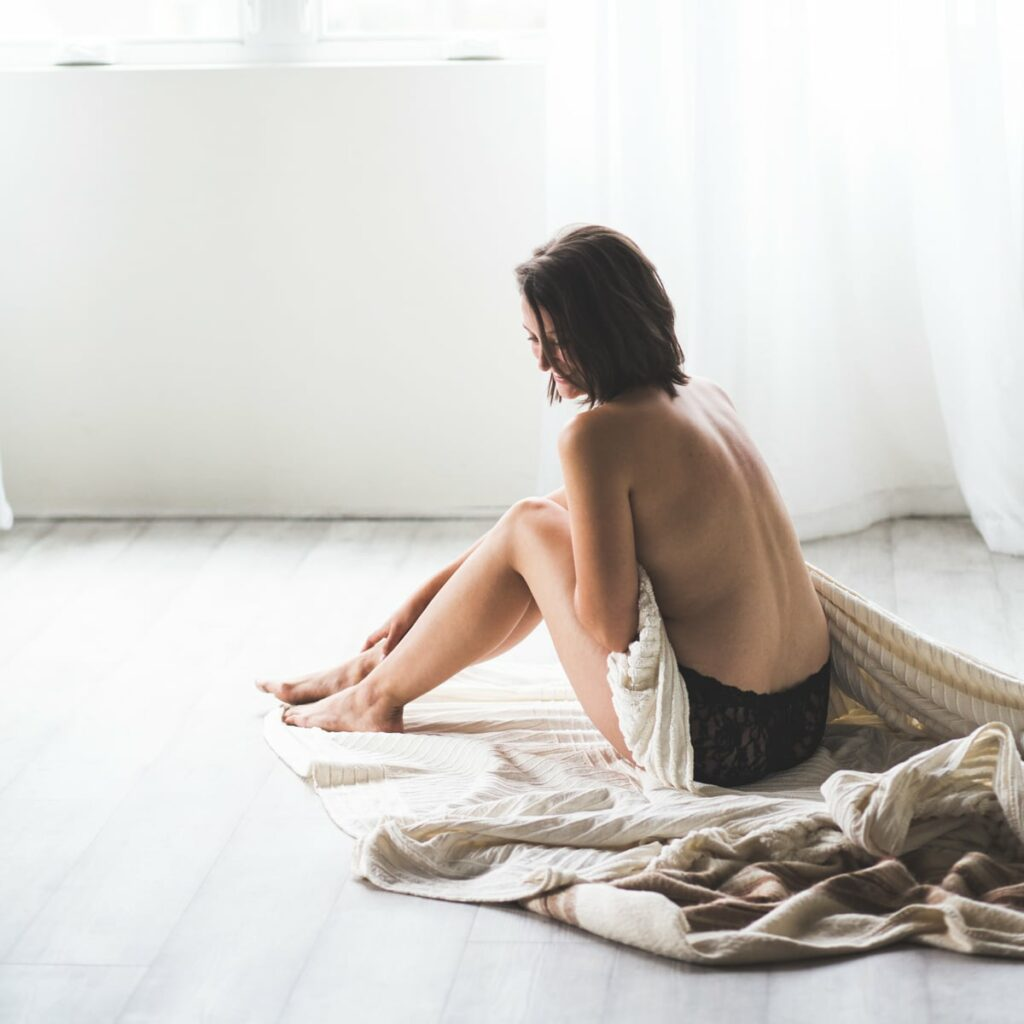 woman sitting with a blanket in a white room
