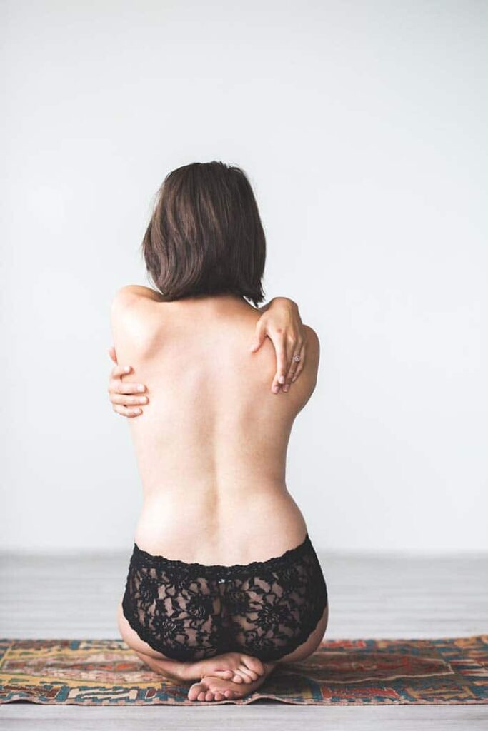 woman sitting on a rug with her back facing the camera