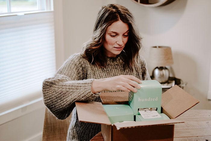 woman opening up Hundred supplements after using discount code