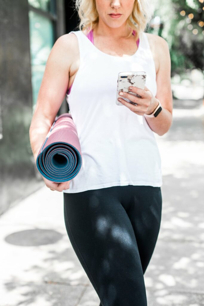 girl with yoga mat and cell phone