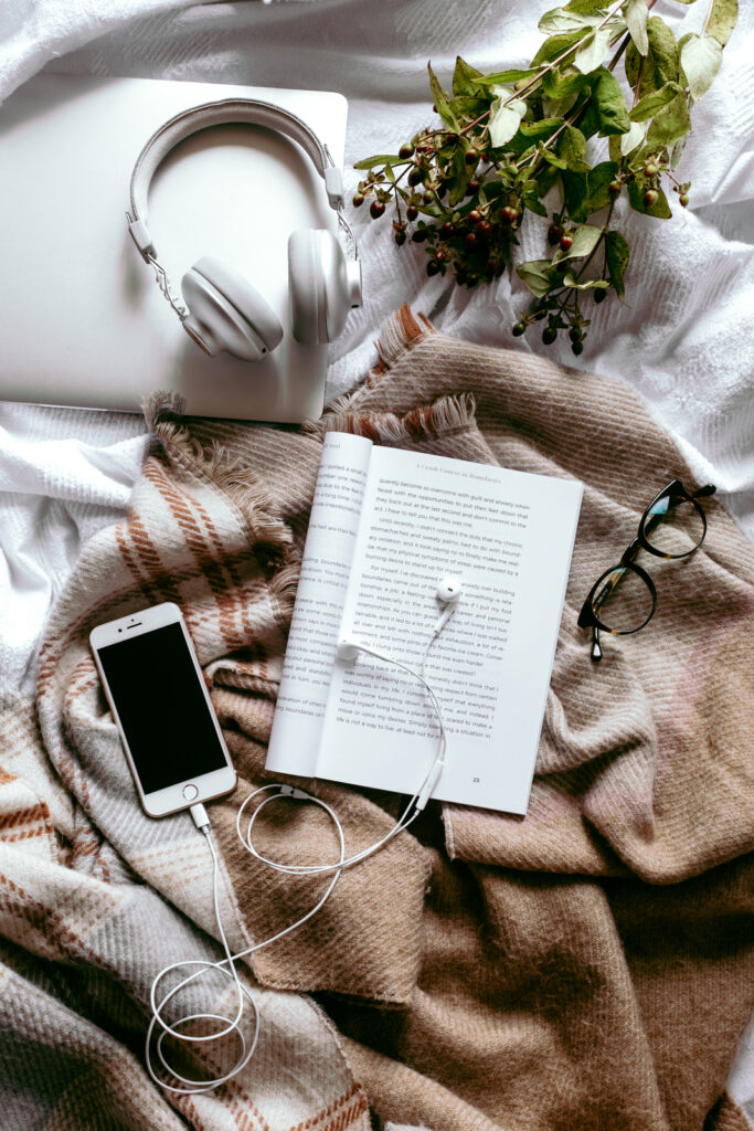 Book and phone on bed with reading glasses