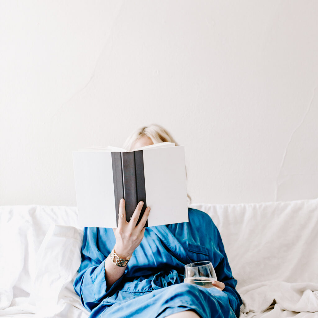 Woman laying in bed reading book