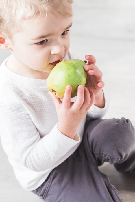 baby biting into green pear for a snack