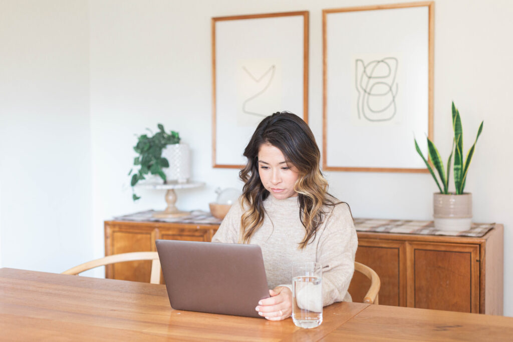 woman working on her laptop at the kitchen table