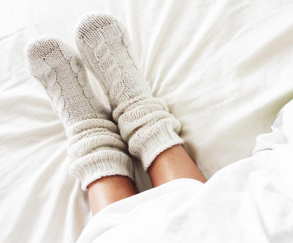 woman wearing cozy socks in bed