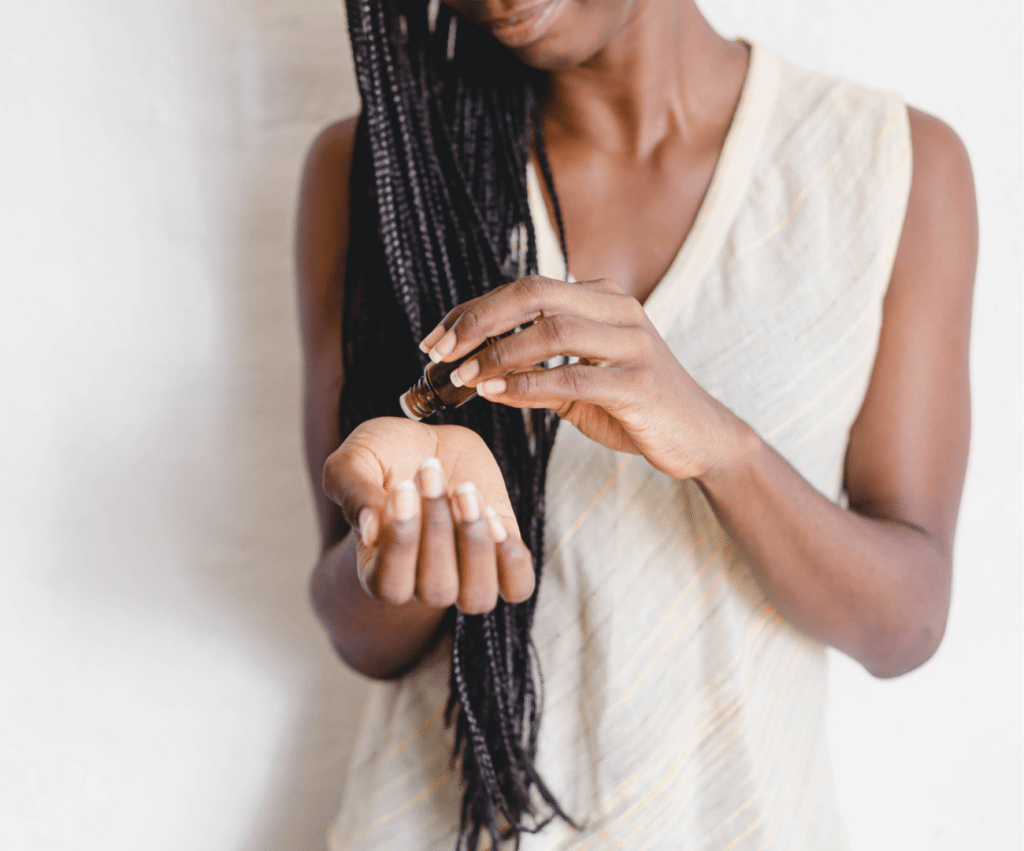 woman putting essential oils on her wrist