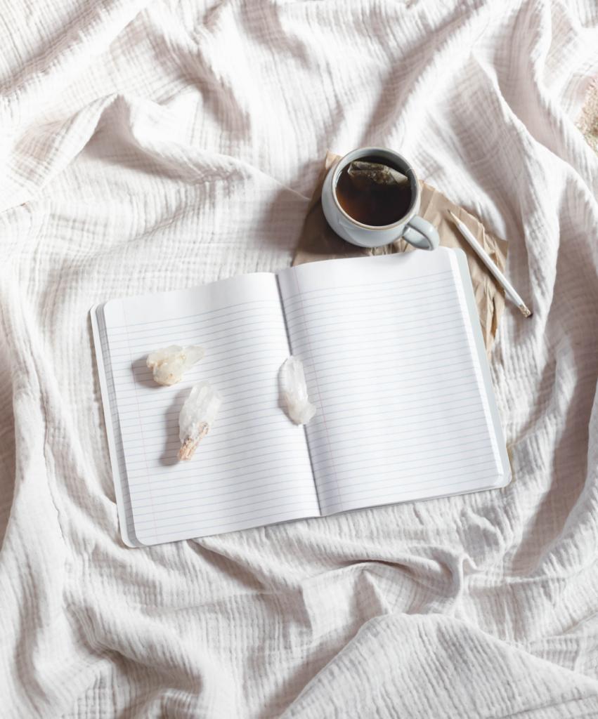 a mug of tea and an open notebook on a linen blanket