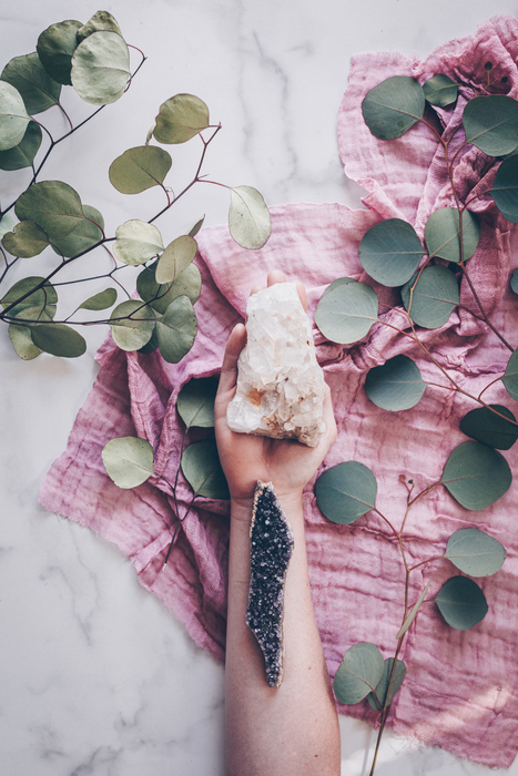 hand holding pink healing crystal and eucalyptus florals around it